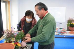 ▲寄せ植えする前に花をポットから取り出した後、行う作業。 先生がお手本を見せながら、参加者の方にコツを伝授しています!